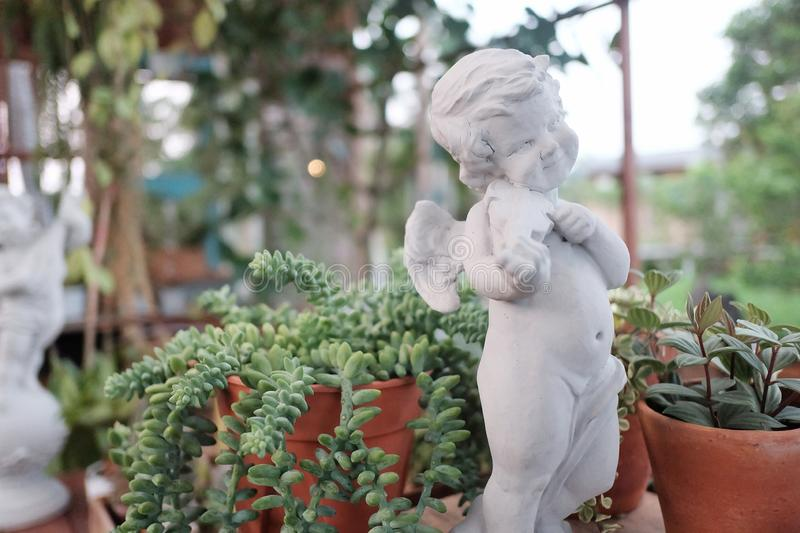 A cute white cupid sculpture playing a violin and staring in a green garden with blurred nature background and bokeh light royalty free stock photo