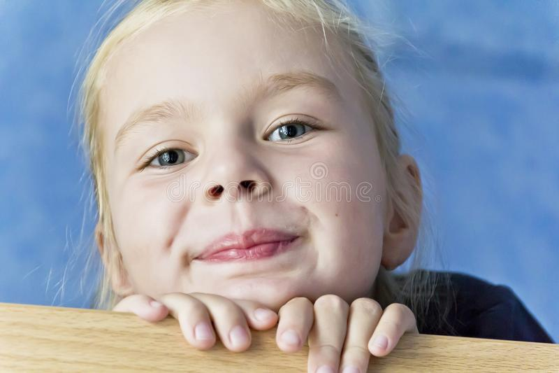 Cute white girl with blond hair. Cute smiling girl with blond hair on blue background stock photos