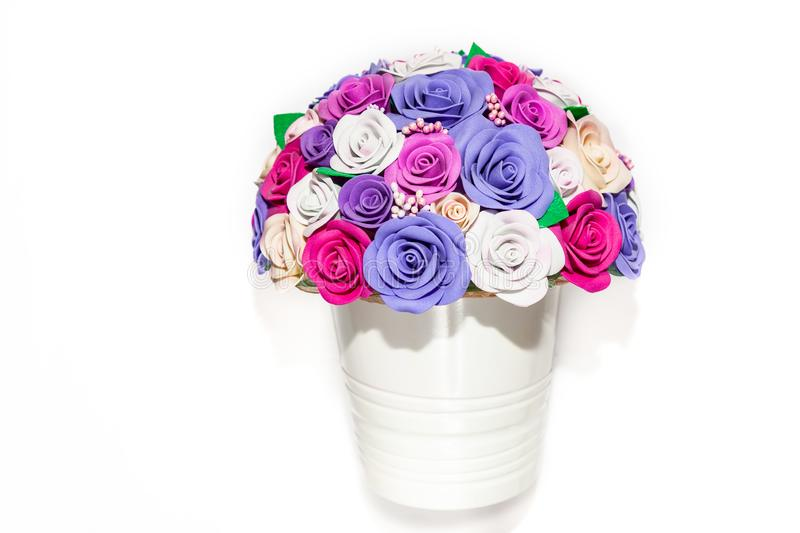 Cute white pot of flowers on an empty background with multicolored decorative roses of pink, purple and lilac colors for interior royalty free stock photos