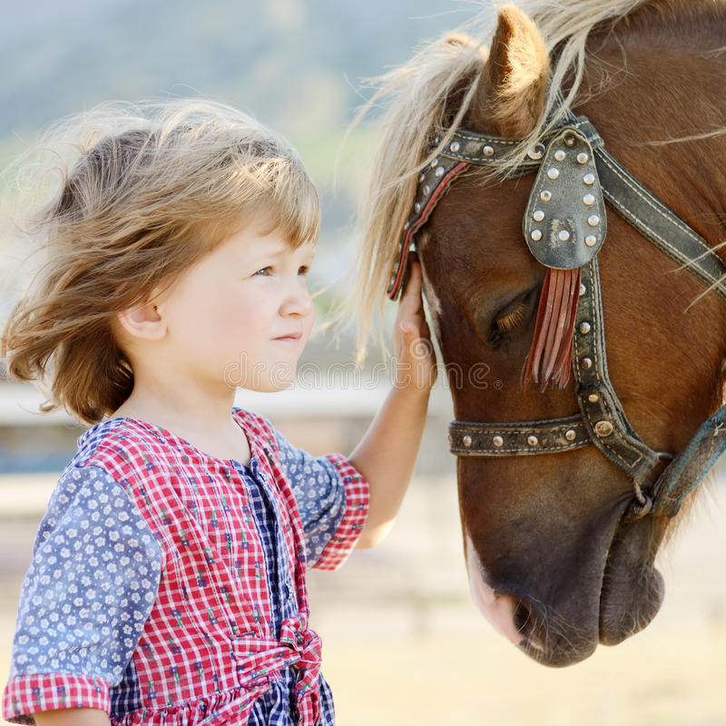 Cute white toddler girl in a rustic style dress caressing brown pony in a field in sunny day royalty free stock images
