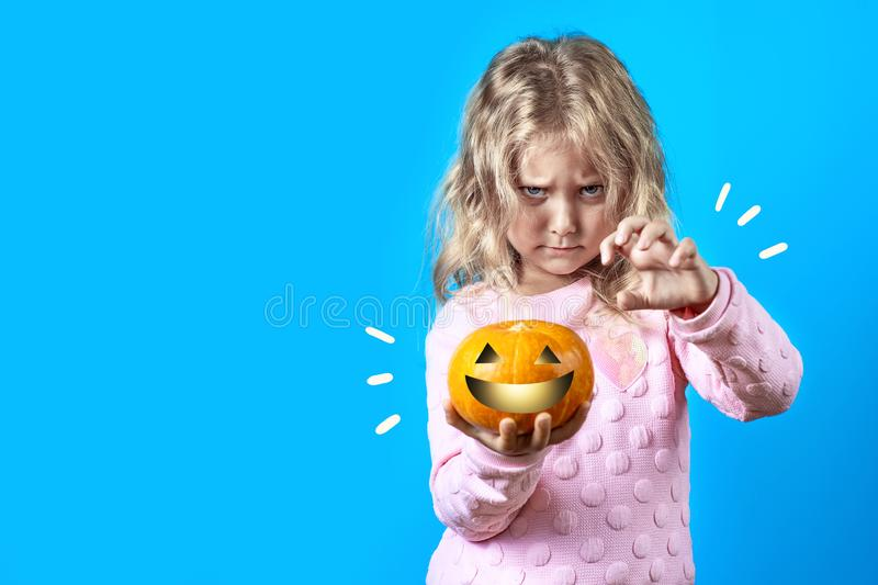 Cute witch girl with blonde hair conjures over a pumpkin on colored background. Cute witch girl with blonde hair conjures over a pumpkin on a colored background royalty free stock images