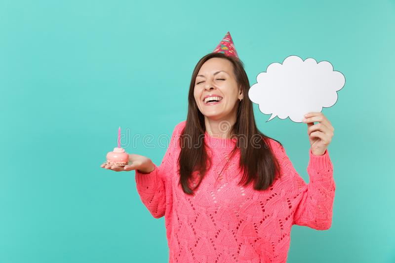 Cute woman in birthday hat with closed eyes hold cake with candle empty blank Say cloud speech bubble for promotional. Content isolated on blue background stock photo