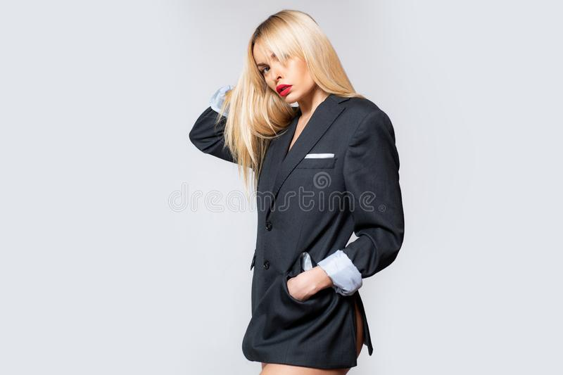 Cute woman in blazer. Blonde girl in a men`s suit in the studio. Portrait of an attractive female model posing on gray stock images
