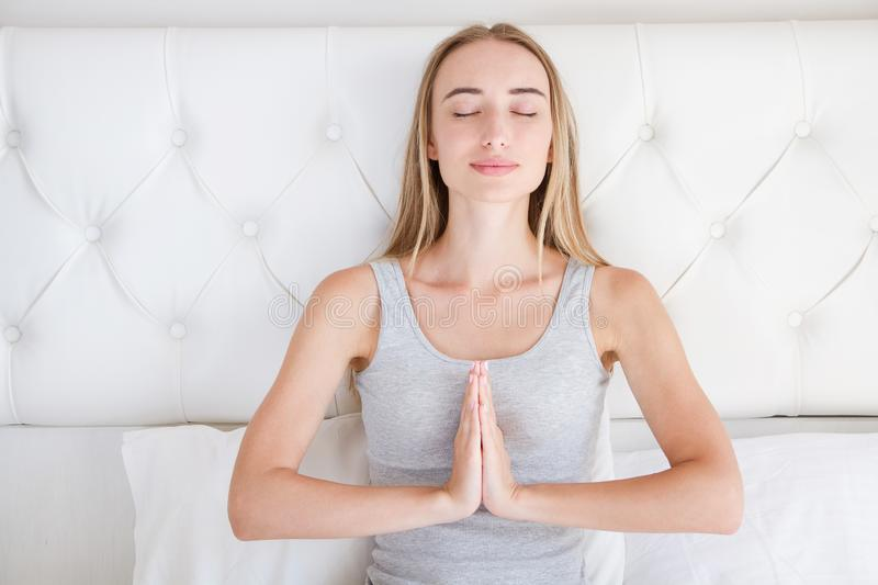 Cute woman with closed eyes in namaste gesture, girl after sleep,relaxation royalty free stock image