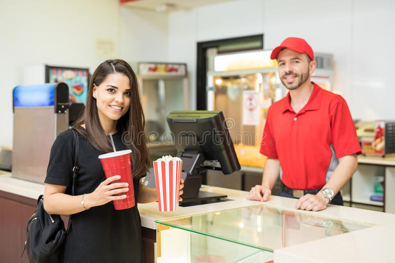 Cute woman in a concession stand. Gorgeous brunette holding a bag of popcorn and a soda next to a concession stand in a movie theater stock images