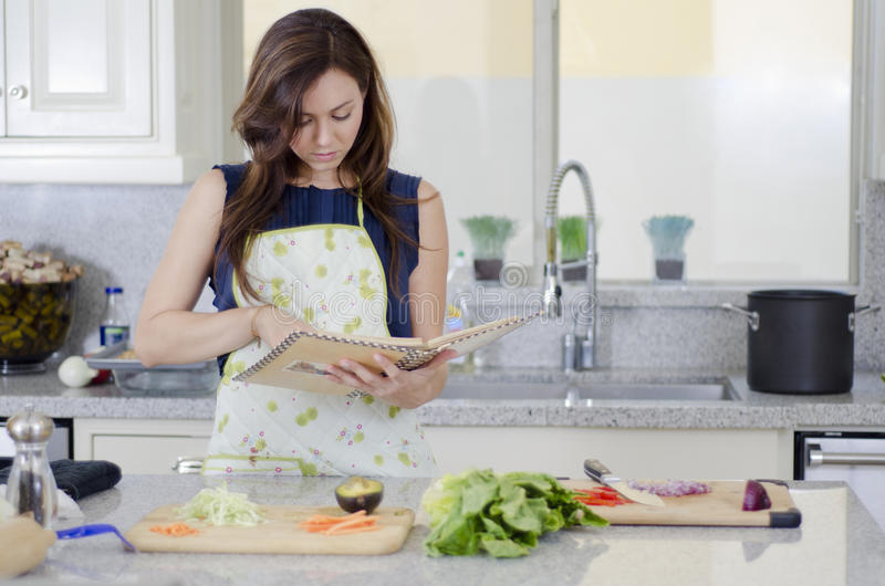 Cute woman cooking a recipe. Young housewife cooking a recipe in the kitchen stock images