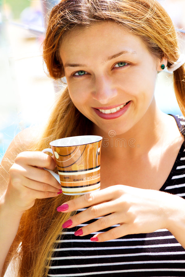 Cute woman drinking coffee outdoor