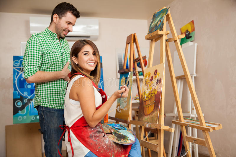 Cute woman enjoying her art class. Beautiful Hispanic brunette working on a painting and getting some advice from her teacher at an art school royalty free stock images