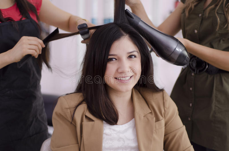 Cute woman getting her hair done. Young beautiful woman getting her hair done in a hair salon royalty free stock photography