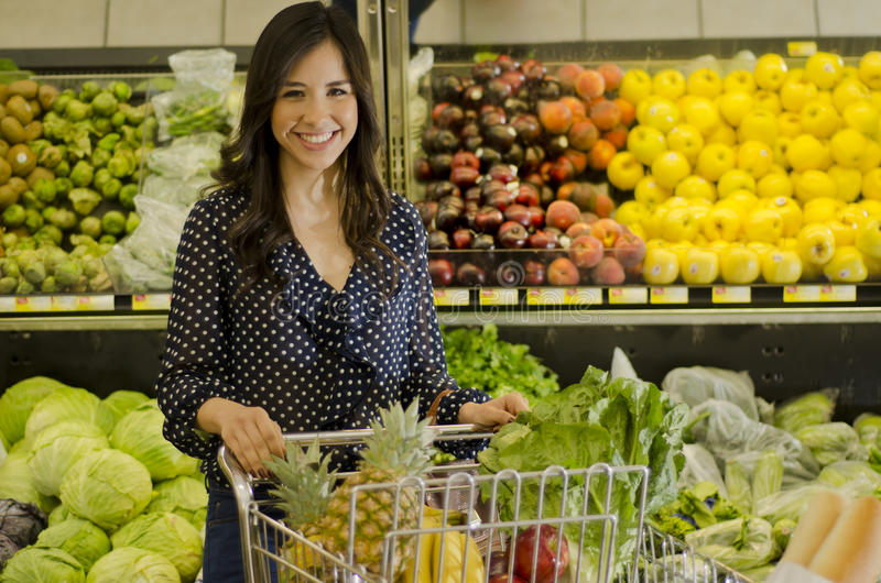Cute woman at the grocery store. Young woman buying some healthy food at the grocery store stock photo