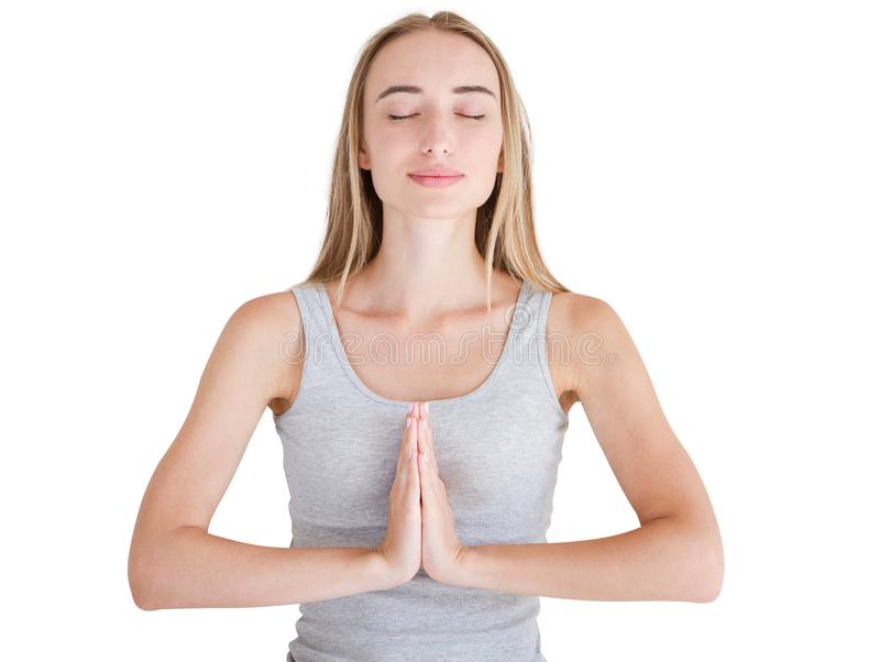 Cute woman holding hands in namaste or prayer, keeping eyes closed while practising yoga and meditating at home alone, having calm stock photo