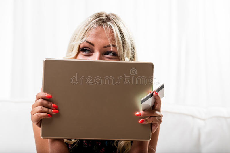 Cute woman holding tablet computer and credit card royalty free stock photos