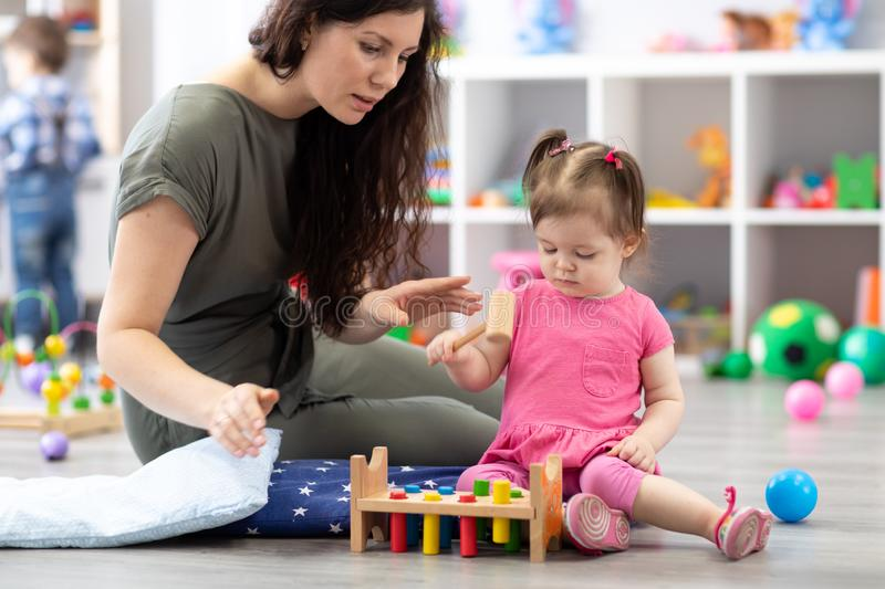 Cute woman and kid playing educational toys at kindergarten or daycare royalty free stock images