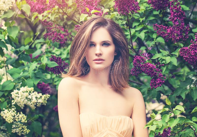 Cute woman on lilac flowers and green leaves background. Perfect model girl outdoor portrait.  royalty free stock photography