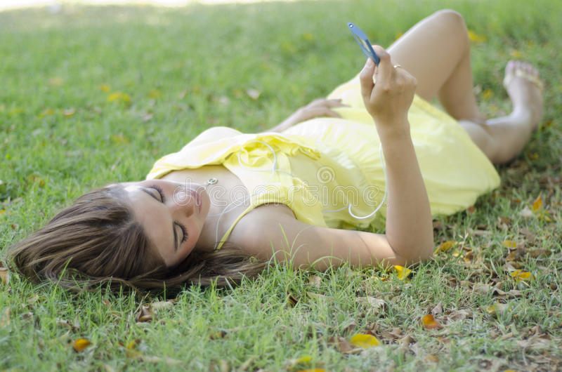 Cute woman listening to music. Young beautiful woman relaxing and listening to music at a park royalty free stock photo
