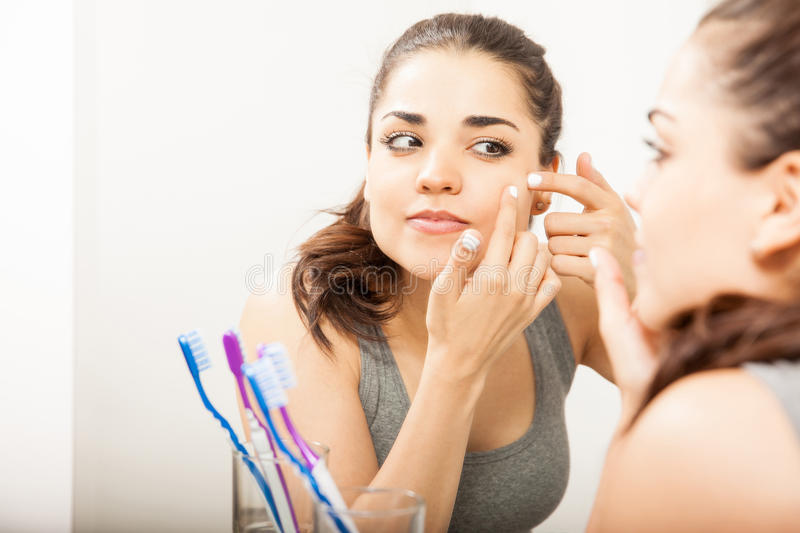 Cute woman looking at a pimple stock photo