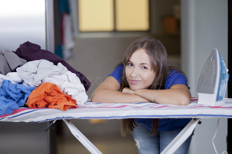 Cute woman overwhelmed with chores. Beautiful young housewife frowning and overwhelmed by too many chores stock photography