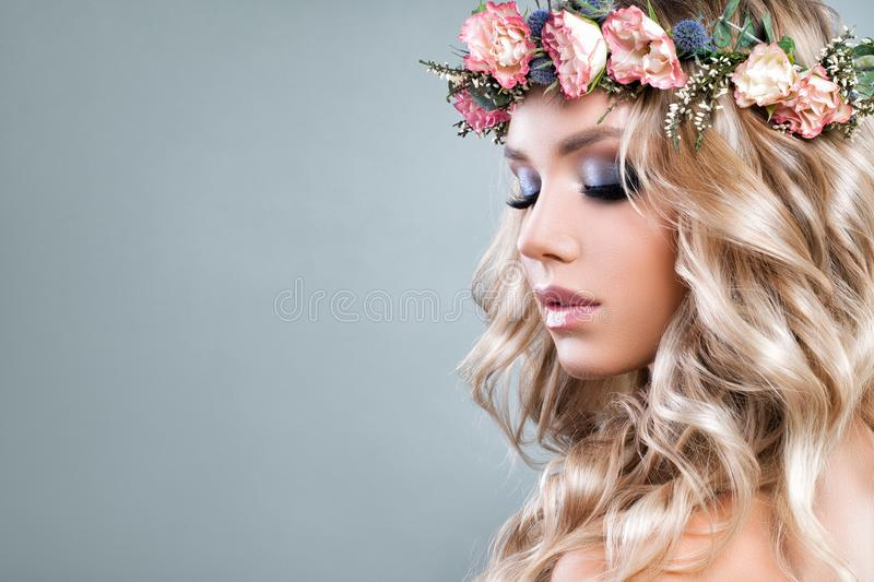 Cute Woman with Pink Roses Flowers and Green Leaves. Wreath, Blonde Curly Hair and Healthy Skin. Skincare and Haircare Concept stock photo