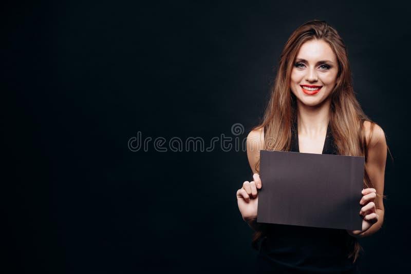 Cute Woman Posing With a Blank Dark Sheet royalty free stock photos