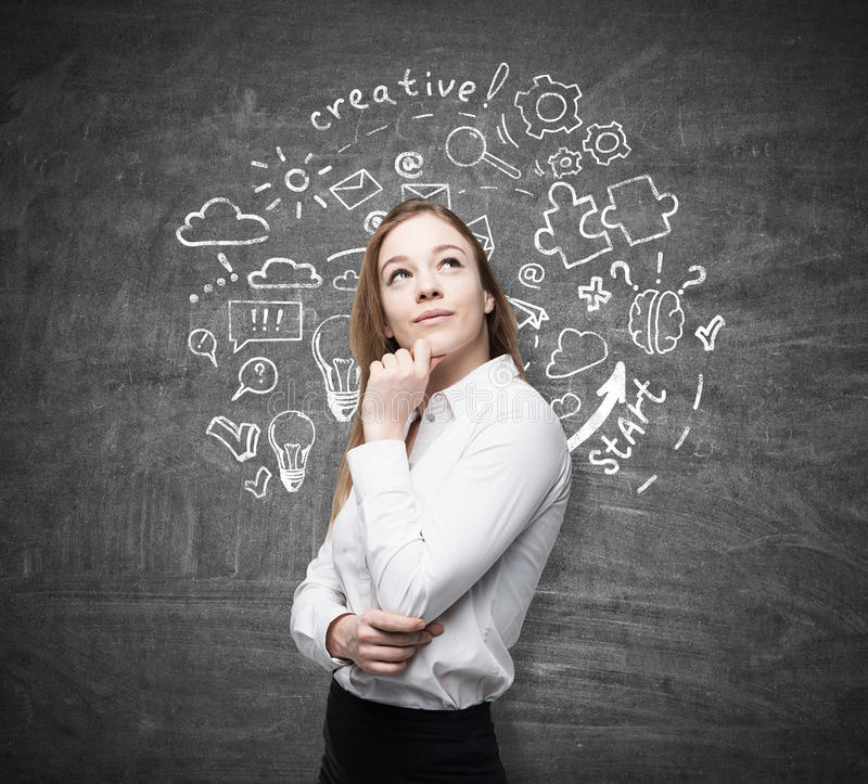 Cute woman and round startup sketch on chalkboard. Portrait of a cute young woman standing near a blackboard with a round startup sketch and thinking royalty free stock photos