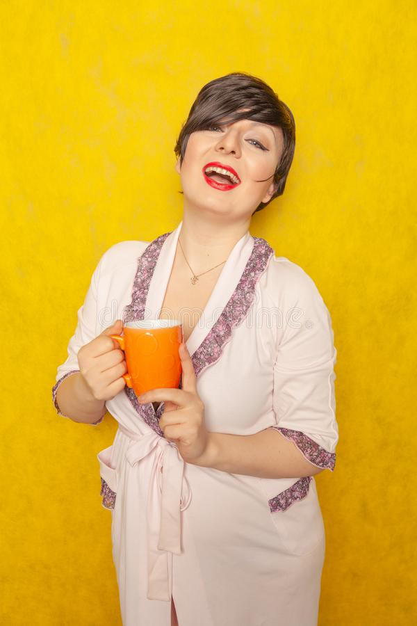 Cute woman with short hair dressed in a cozy pink Bathrobe and drinks a tea from an orange Cup on a yellow solid background in the. Studio alone stock images
