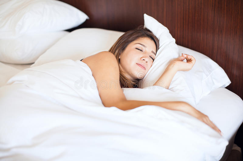 Cute woman sleeping on a bed royalty free stock photography