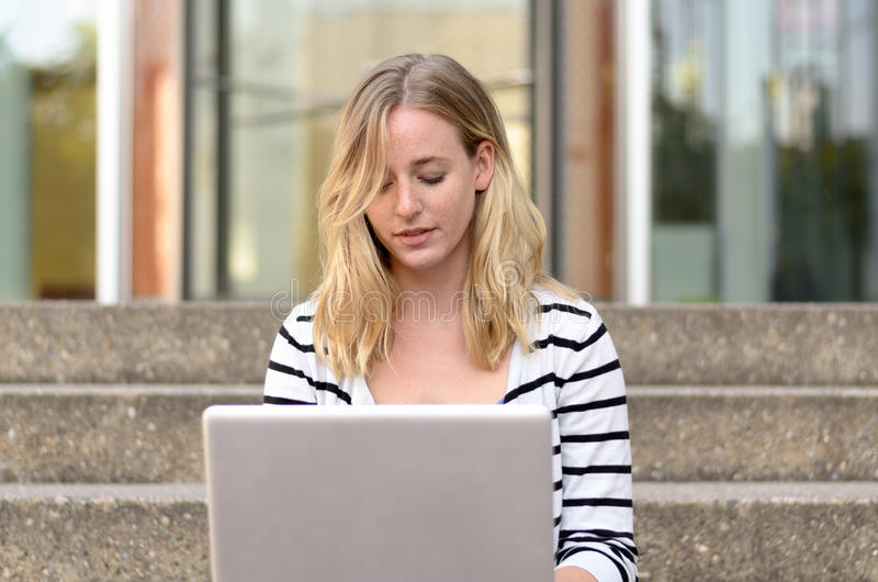 Cute woman in striped shirt typing on computer royalty free stock image