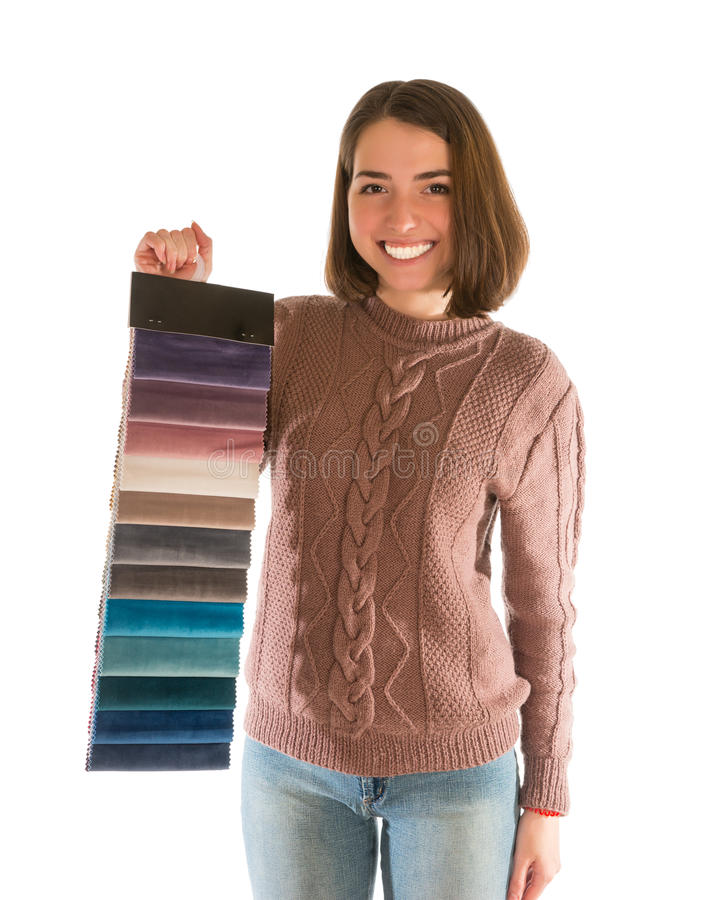 Cute woman in sweater holding fabric swatches. Isolated on white background royalty free stock photography