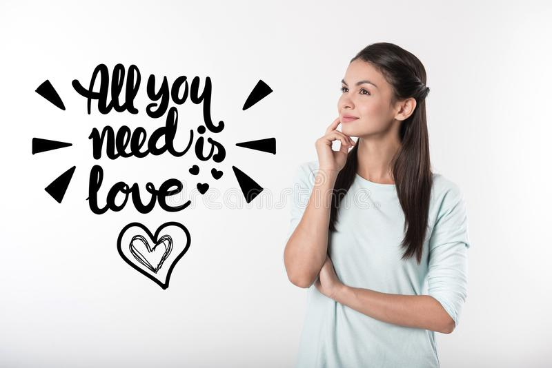 Cute woman touching her face and dreaming about finding love royalty free stock photos