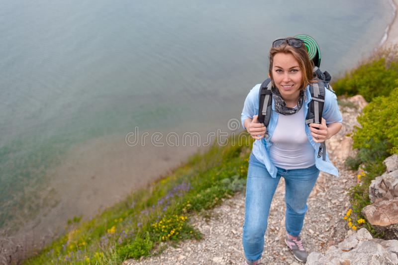 Cute woman tourist walking along a mountain trail. Hiking and sports stock photos