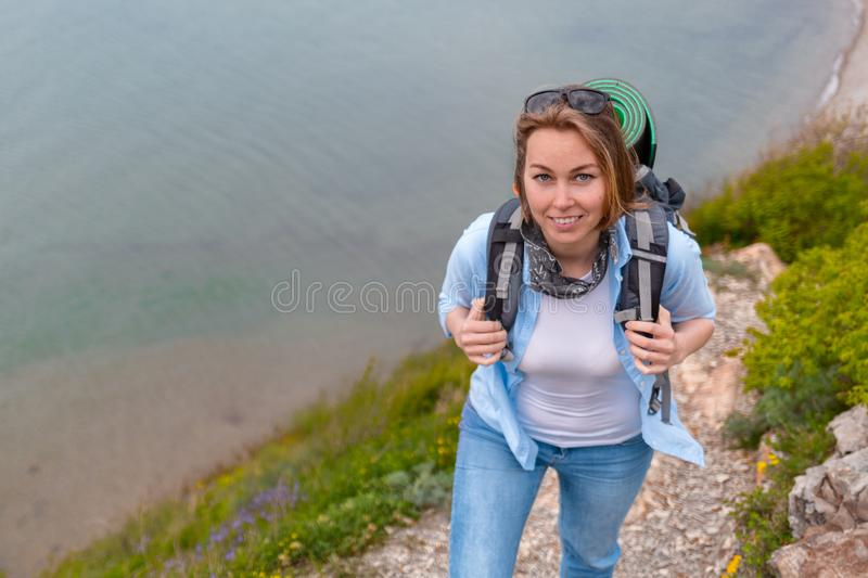 Cute woman tourist walking along a mountain trail. Hiking and sports. Close up stock image