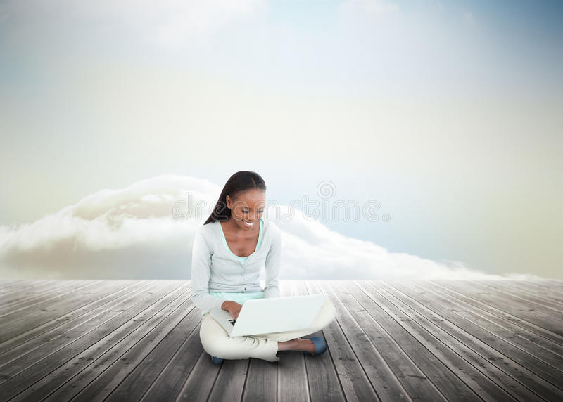 Download Cute Woman Using Laptop Over Wooden Boards Leading Out To The Horizon Stock Photo - Image: 31799616