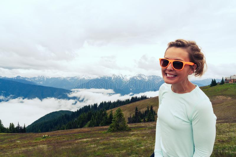 Cute woman wearing neon sunglasses poses at Hurriance Ridge in Olympic National Park in Washington State. Cute woman wearing neon sunglasses poses at Hurricane royalty free stock image