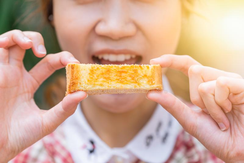 Cute women holding butter toast eating in the morning royalty free stock photography
