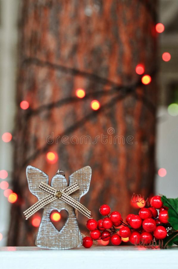 Cute wooden angel decoration on the Christmas tree on the background of red lights on the street stock image