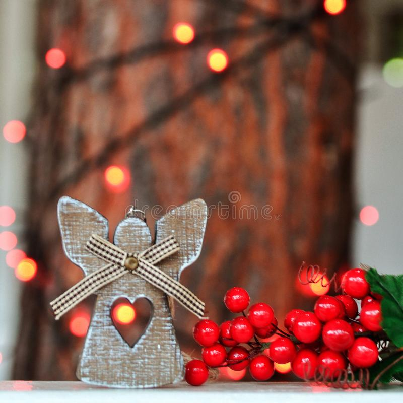 Cute wooden angel decoration on the Christmas tree on the background of red lights on the street royalty free stock photos