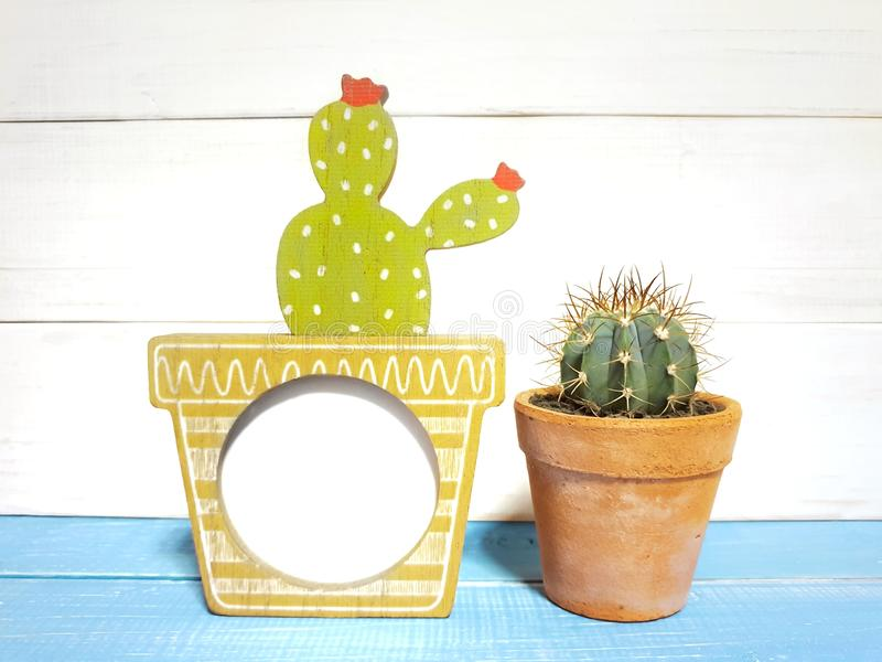 Cute wooden frame handicraft and cactus in clay pots. Isolated a isolated on wooden background with copy space.home home decoration. houseplant is popular in stock images