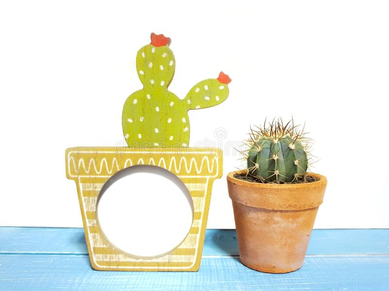 Cute wooden frame handicraft and cactus in clay pots isolated a isolated on wooden background. With copy space.Home decoration. Houseplant is popular in royalty free stock photography