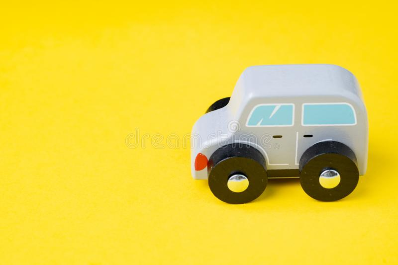 Cute wooden small toy car parking on vivid yellow background, car leasing, rental or insurance or automobile market concept royalty free stock photo
