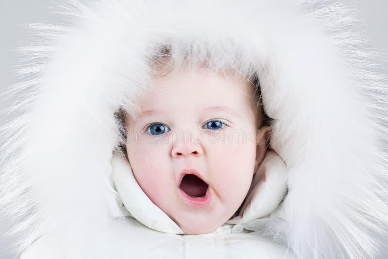 Cute yawning baby girl wearing huge white fur hat stock images