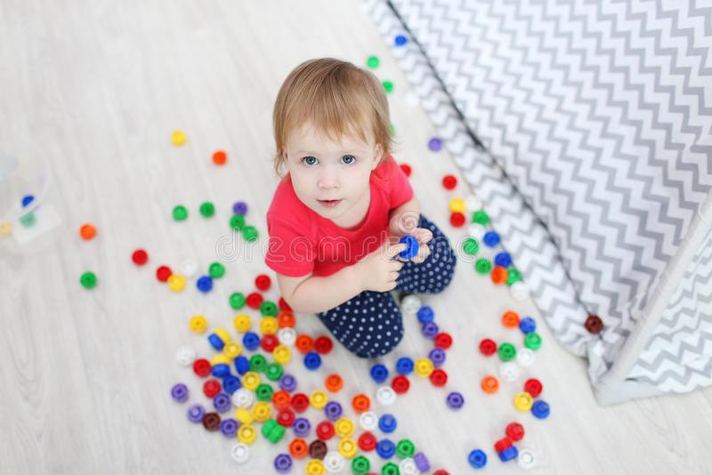 Cute 1 years blue-eyed baby girl plays multicolored meccano at h. Cute 1 years baby girl plays multicolored meccano at home stock photos