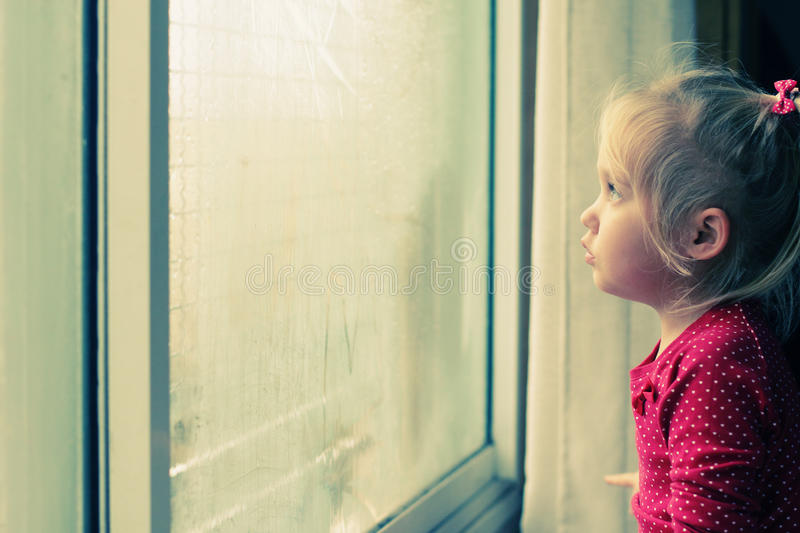 Cute 4 years old girl. Looking through the window royalty free stock images
