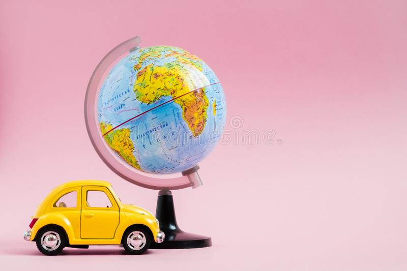 Cute yellow little retro car with world globe sphere. Travel concept. Planning summer vacations stock images