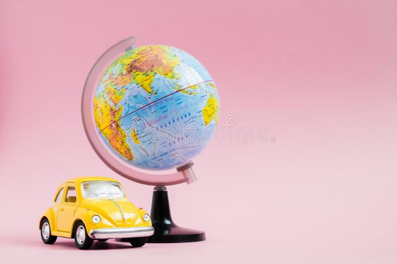 Cute yellow little retro car with world globe sphere. Travel concept. Planning summer vacations stock photo
