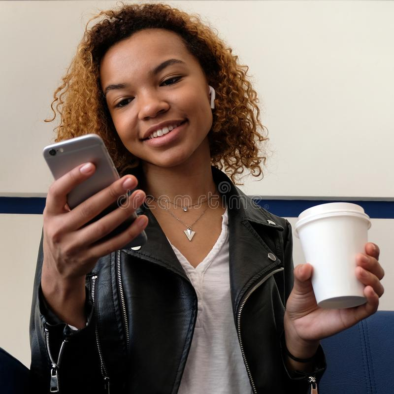 A cute young African American woman is holding a telephone and a paper cup of coffee. Headset without wires in the ear. Listening. To music, talking on a cell stock photos