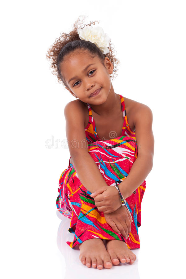 Cute young African Asian girl seated on the floor stock image