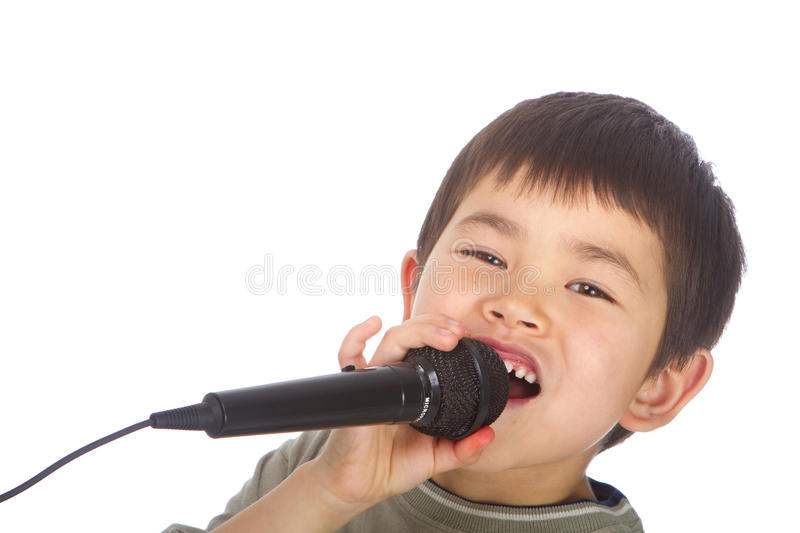 Cute young asian boy singing into a microphone stock image