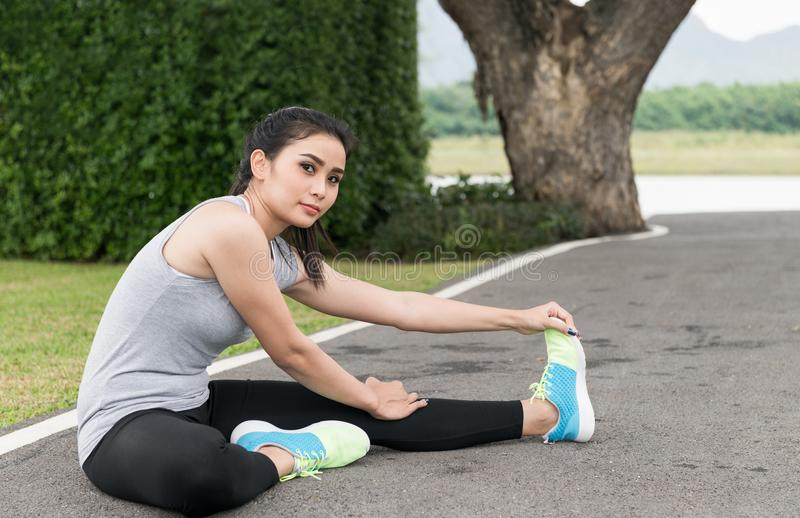 Cute young asian woman stretching after run on track stock image