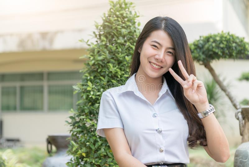 Cute young asian woman in uniform student show v sign finber, sm stock photography