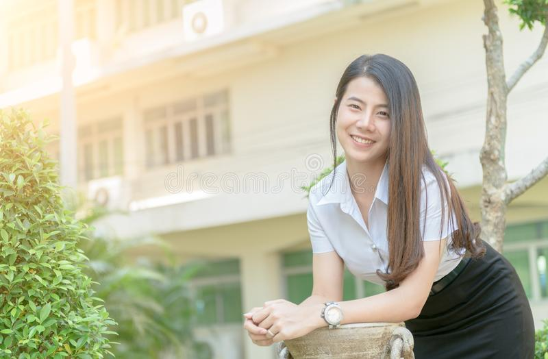 Cute young asian woman in uniform student smile in campus stock image